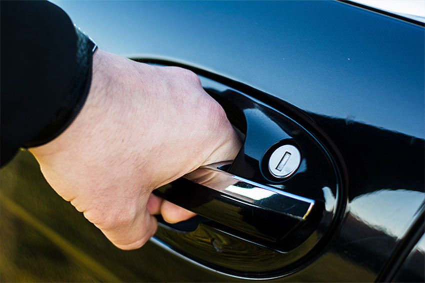 Close up of man's hand opening a black car.